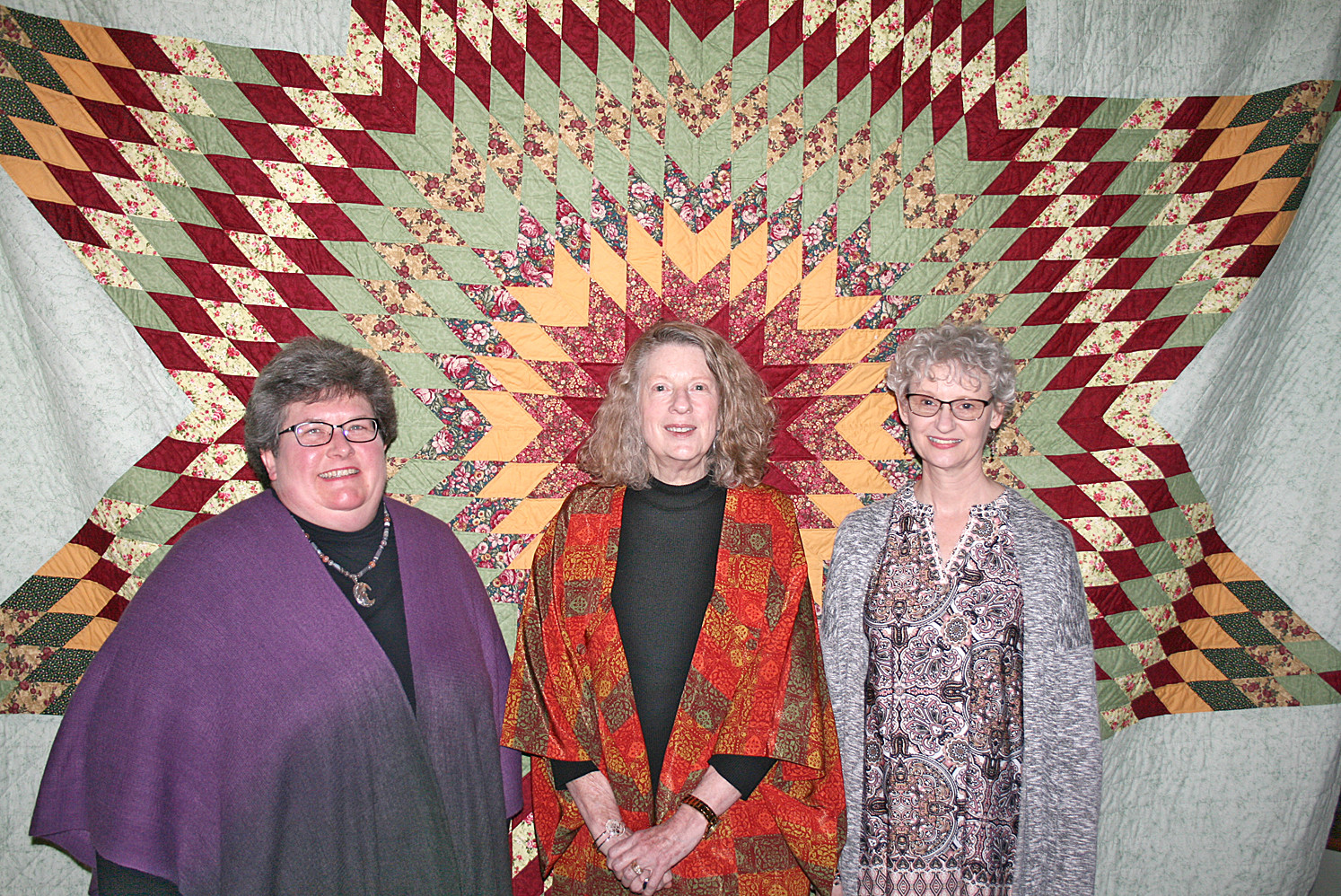 The winners of the Stitches in Time event's quilt challenge lined up in front of the large quilt in the Museum Center at Five Points' lobby. From left are Johanna Kosik, third place; Shirley Prince, second place; and Denise Ohlman, first place.