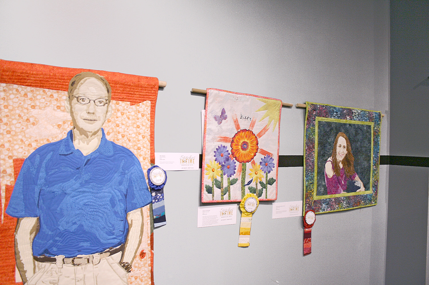 The winners of the Art Quilt challenge stand together. From left are first place, second place and third place.