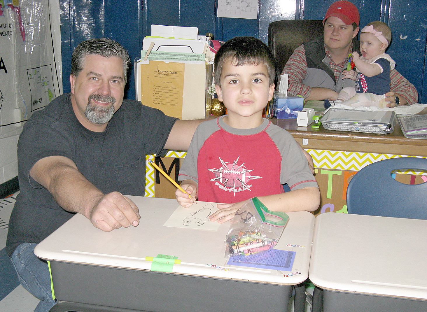 Gage Chastain and his dad work together to draw a Lorax, as part of the Dr. Seuss in schools initiative at Hopewell Elementary.