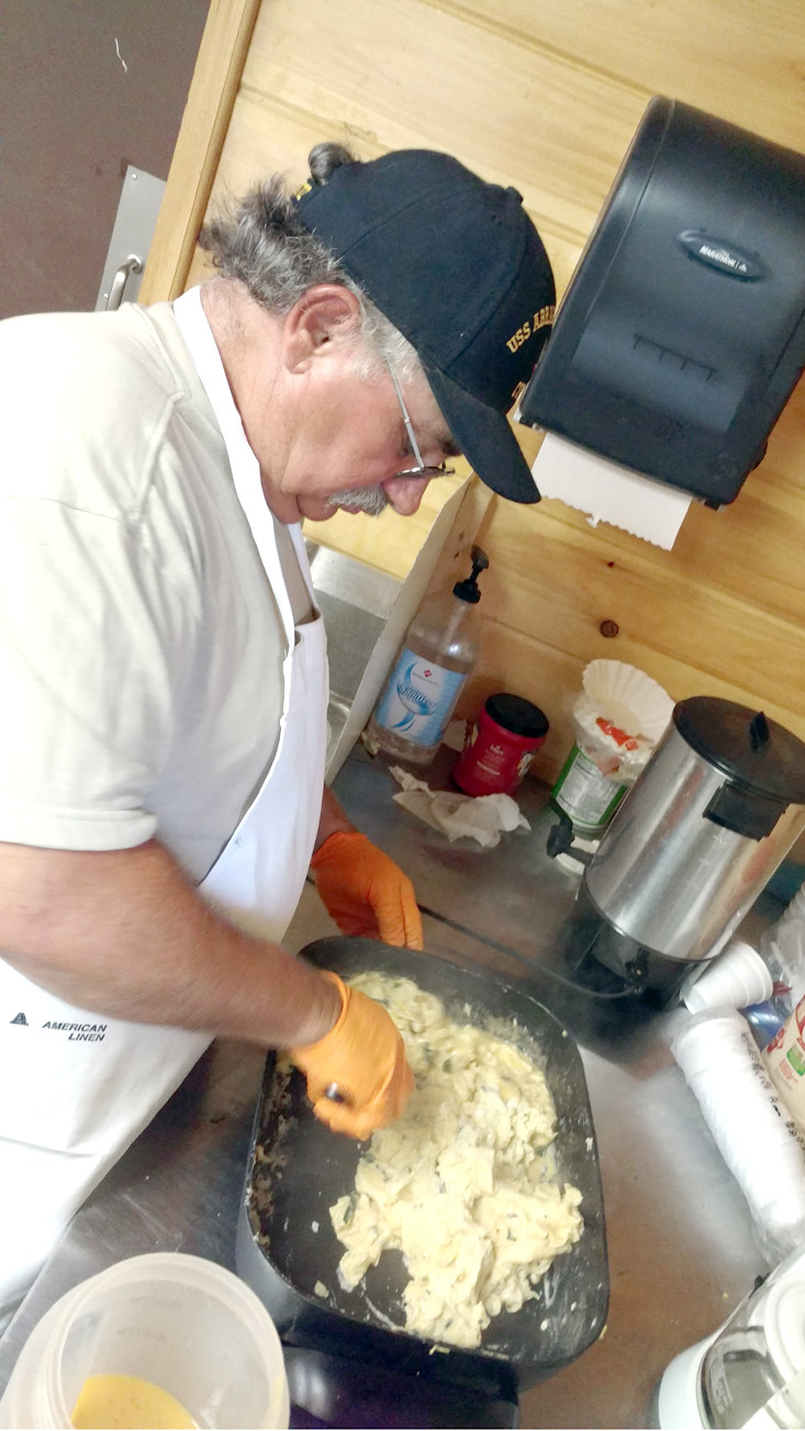 A VOLUNTEER mixes up the tradition meal of ramps in eggs, streaked meat, white beans, cornbread and potatoes.