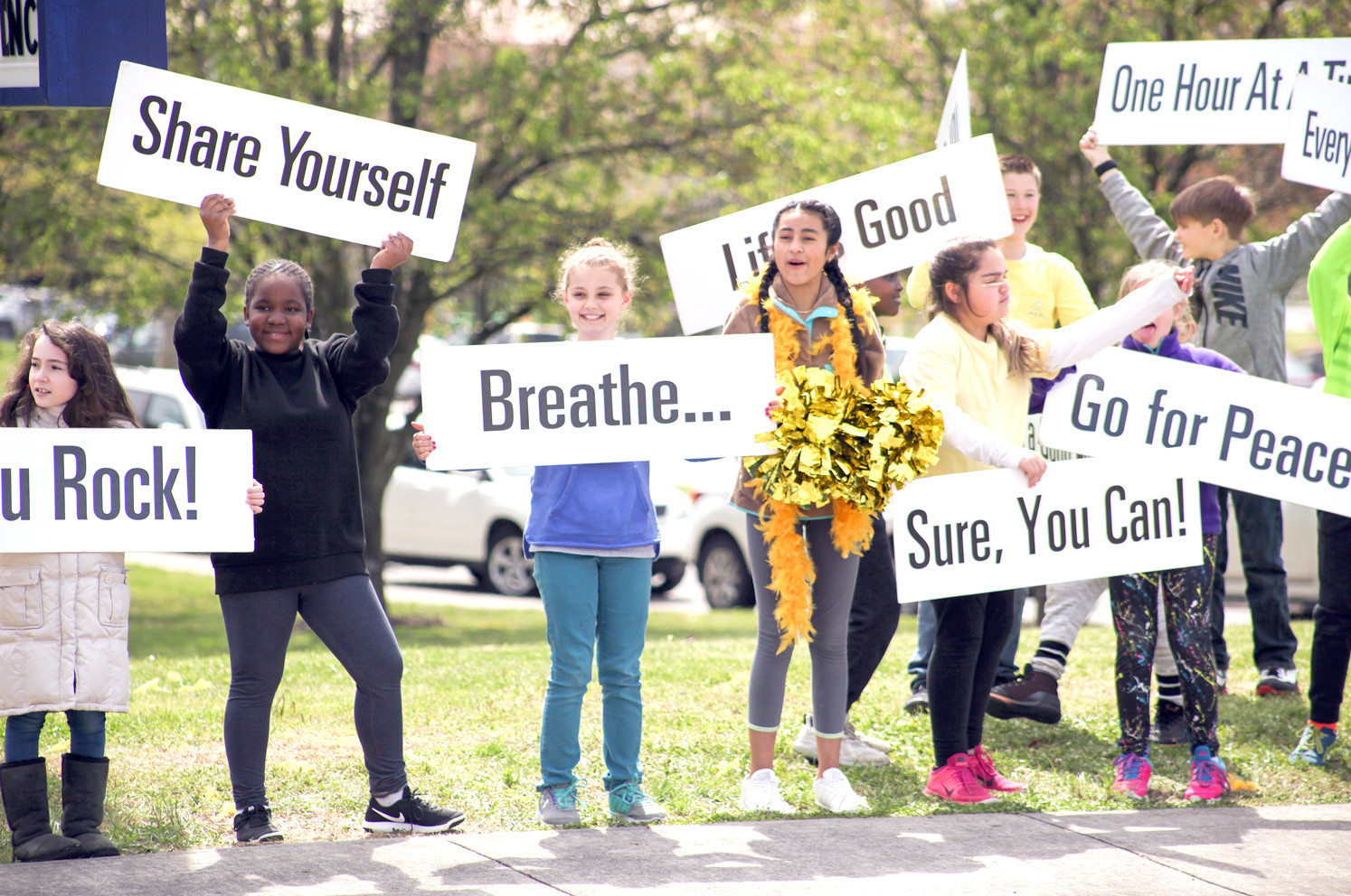 A GROUP OF E.L. ROSS students wave at passing cars during the Happiness Sprinkling event on Thursday.