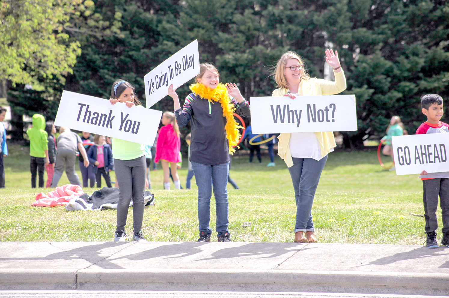 E.L. ROSS STUDENTS Christina Assal, left, and Anastasia White along with the E.L Ross Guidance Counselor, Emily Elliott, right, raise their Happiness Sprinkling signs to honking motorists during the event last week.