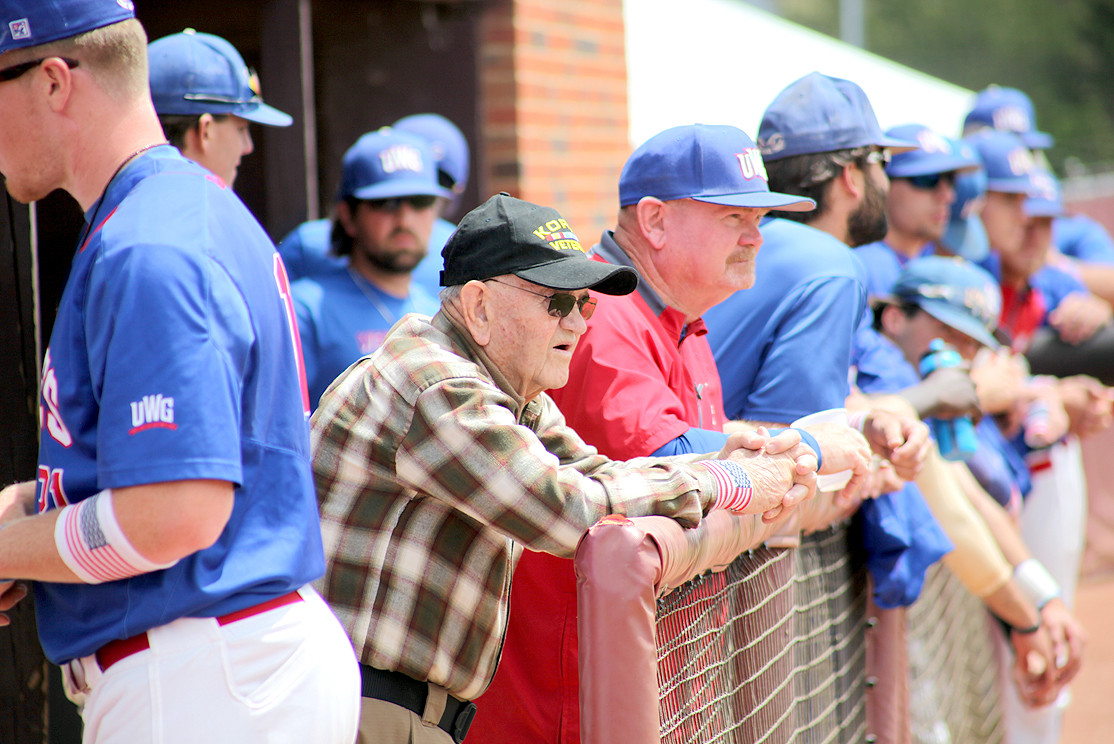 "BILL ""SARGE"" FITE, a Korean War veteran, center, and his son and Coach of the West Georgia baseball team, Skip Fite, survey the field prior to the Military Appreciation Day game."