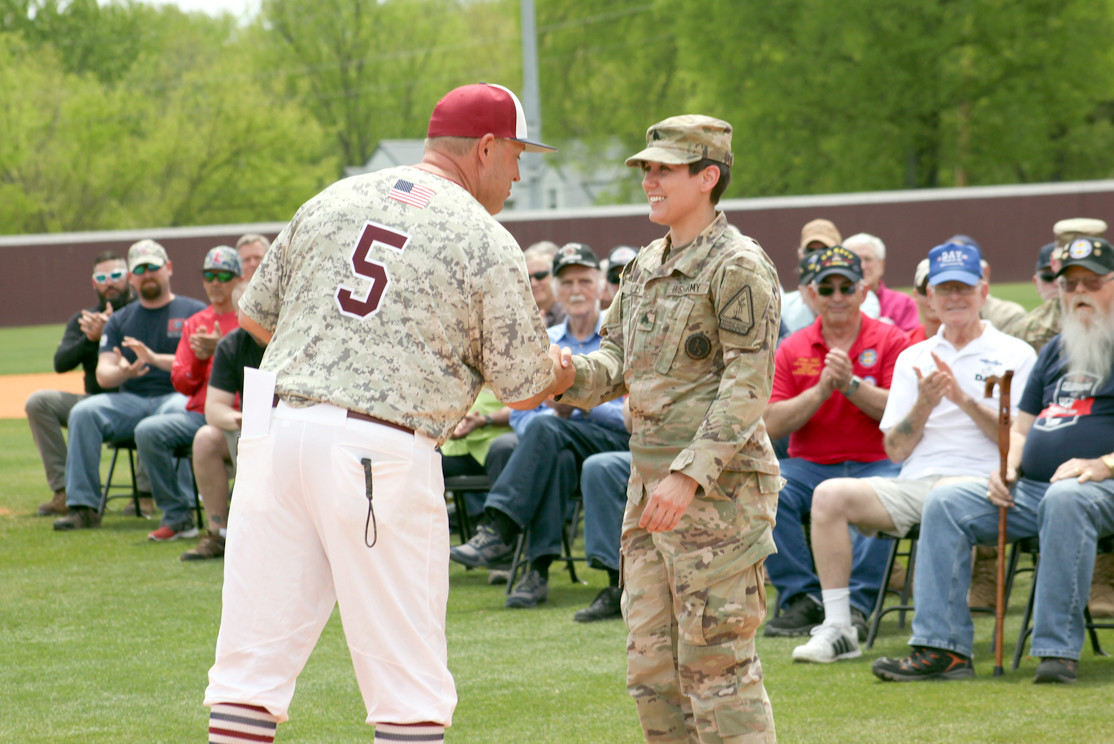 LEE UNIVERSITY Baseball Coach, Mark Brew, left, presents Sgt. Jackie Walls from the National Guard with a plaque for their help in support of the Military Appreciation Day event.