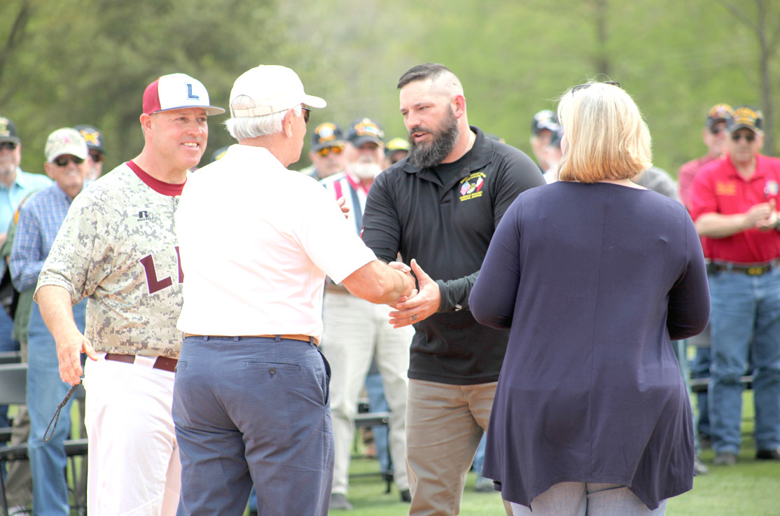 FIRST RECIPIENT of the Bobby Taylor Memorial Scholarship, Master Gunnery Sergeant Sam Dean (USMC), center, shakes hands with Scott Taylor, Bobby Taylor's son, at the scholarship recognition ceremony.  Also shown, from left ,are Lee University Baseball Coach, Mark Brew and Christy Goza, executive vice president of Bank of Cleveland.