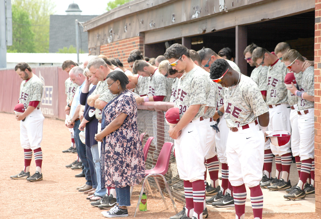 THE LEE UNIVERSITY baseball team and honored guests bow their heads during the moment of silence honoring those from the armed services who have lost their lives or have gone missing in the line of duty.