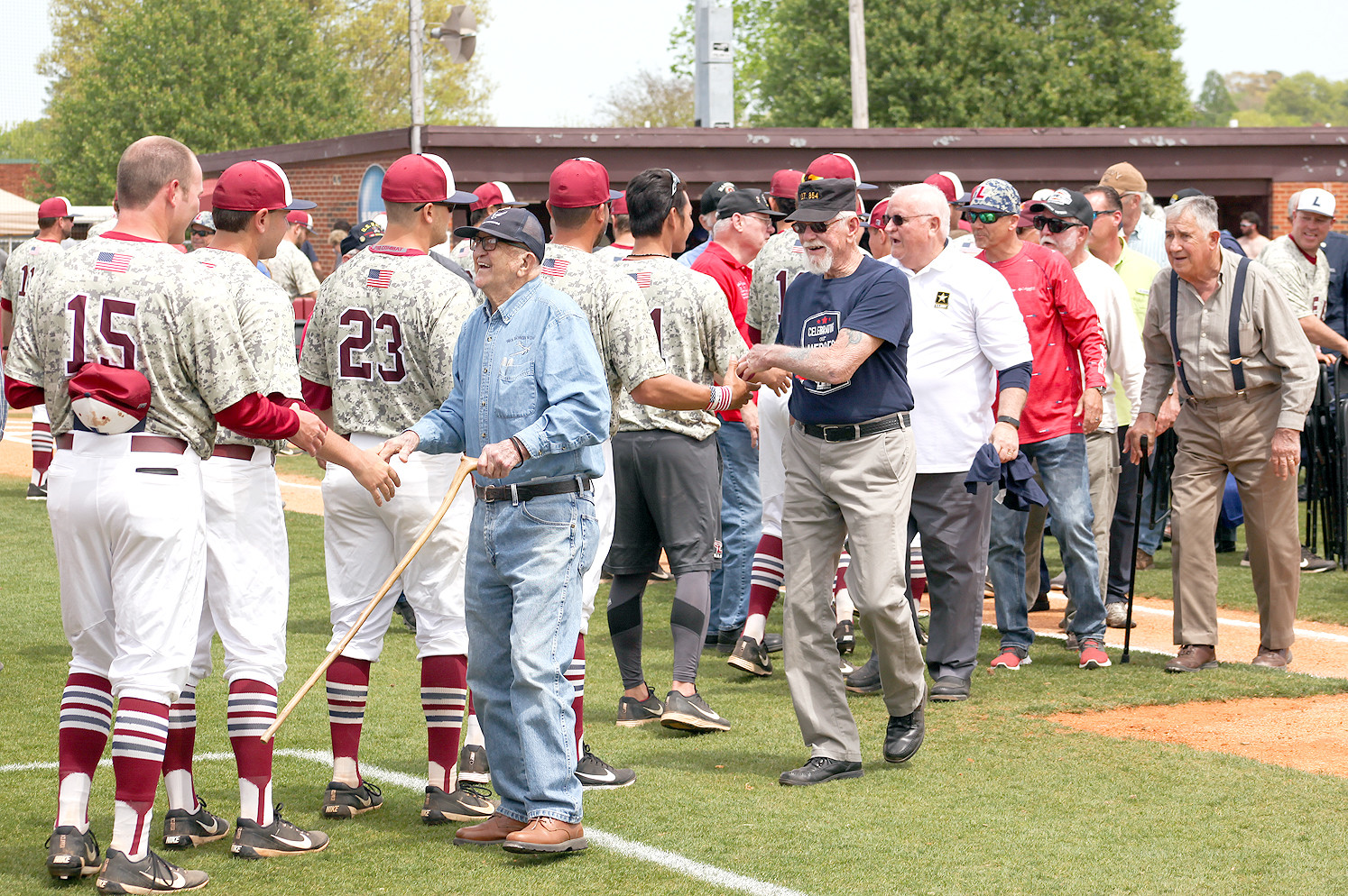 THE LEE UNIVERSITY baseball team members shake hands with the veterans as the leave the field at Saturday's Military Appreciation Day event.