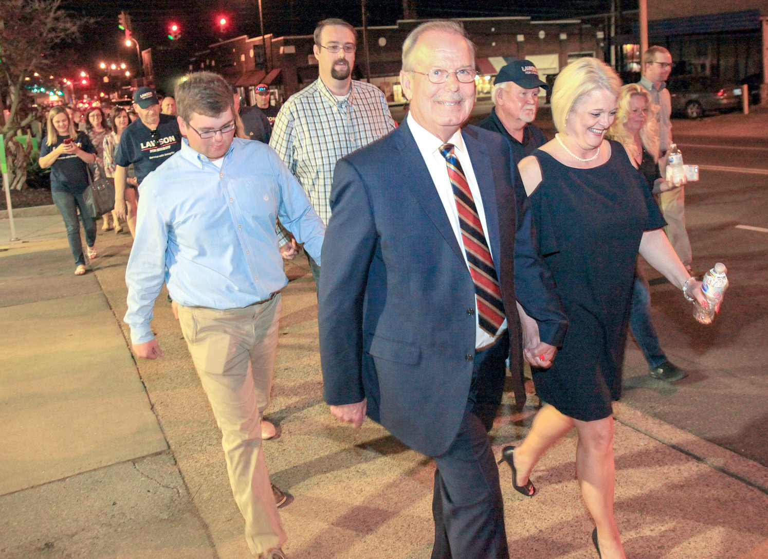 STEVE LAWSON, center, and his wife, Connie, lead the string of supporters attending the Museum Center election-night gathering on a walk to the Bradley County Courthouse Plaza to celebrate his impending win in the Bradley County sheriff's race.