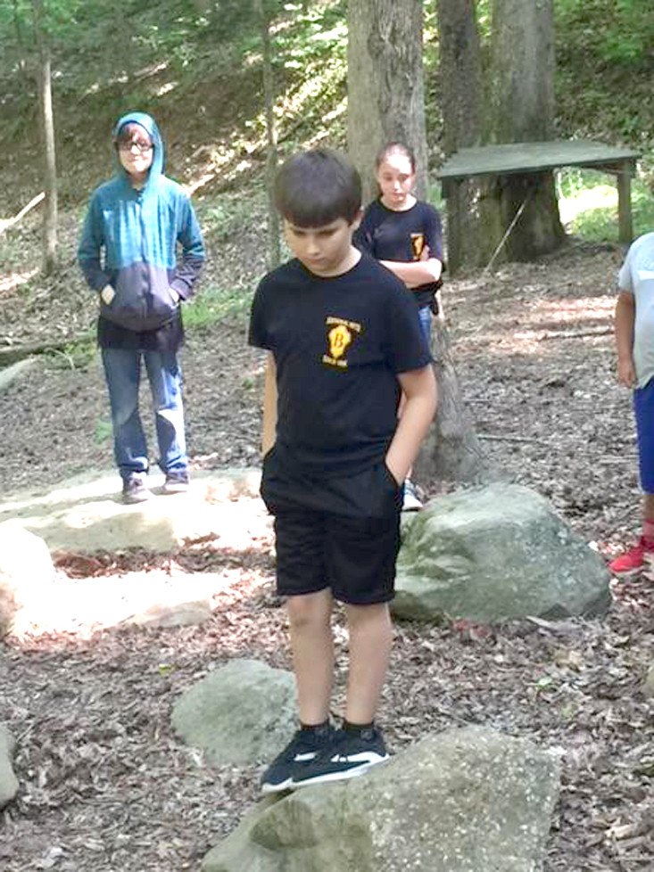 Park View student Dylan Heffington decided which path to take in a leadership activity at Camp Living Stones. Gage Hedrick looks on.