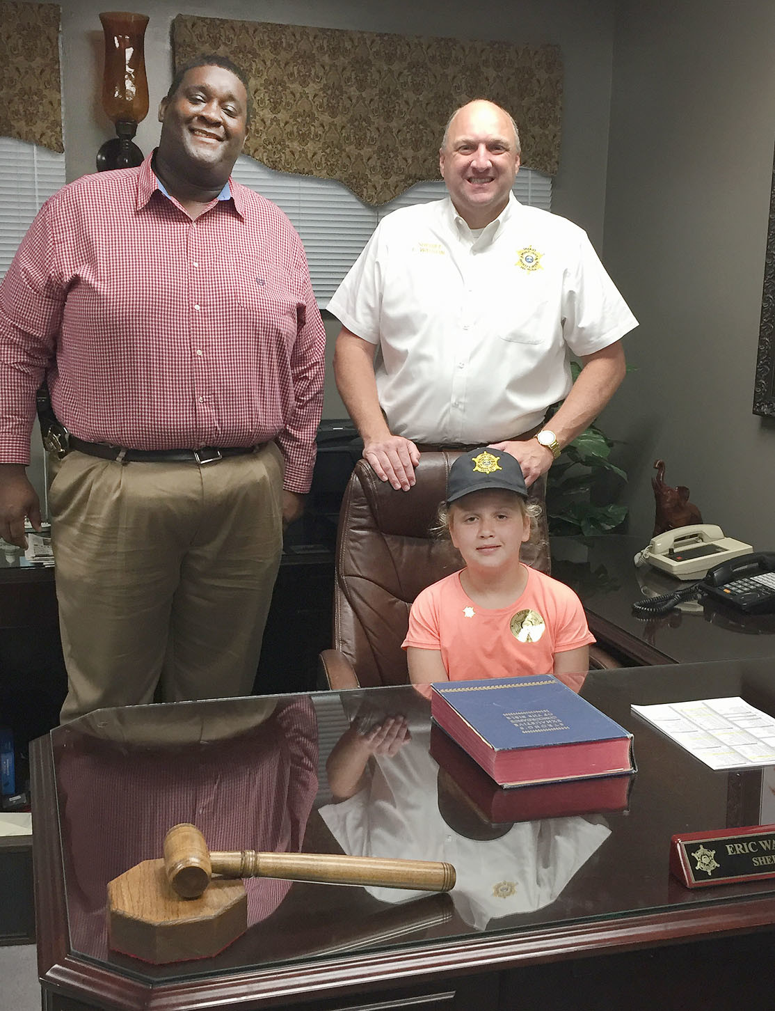 "Savannah Medek, who will be a fifth-grader at Black Fox Elementary School in the fall, recently served as Bradley County's ""Sheriff For A Day."" Standing behind ""Sheriff Medek"" and awaiting their orders are Chief Deputy James Bradford and Sheriff Eric Watson."
