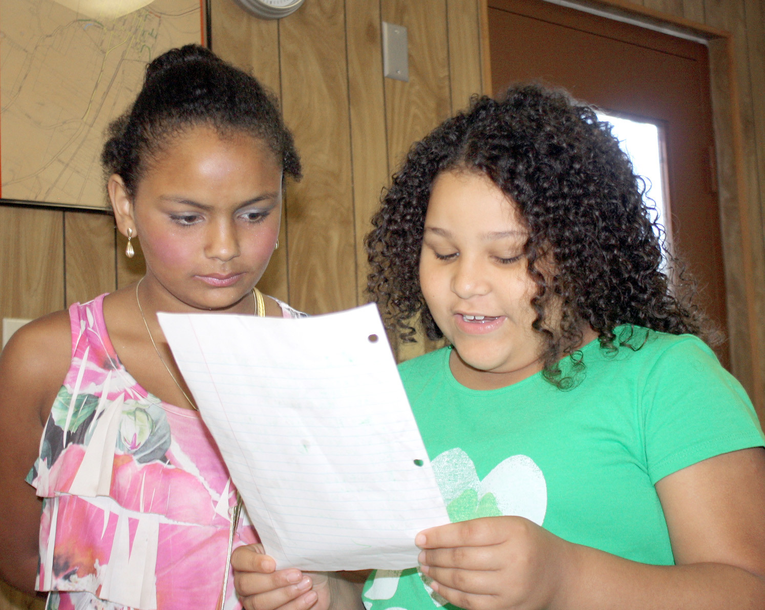 TWO CHARLESTON 9-year-old girls have some definite ideas for improvements at Charleston's Hoyt Berry City Park. Above, Tonya Bradley, left, and Alaysia Lattimore read a letter listing their improvement suggestions; and they've already raised $153.53 for the tentative project at a gospel singing fundraiser.