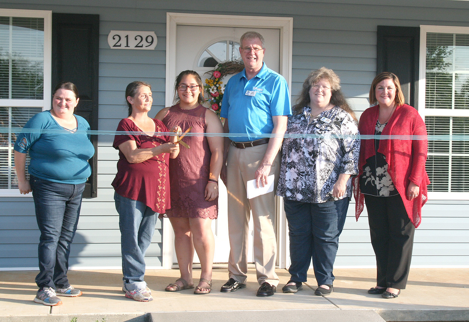 RIBBONS WERE CUT in front of each of the three homes at the Habitat for Humanity of Cleveland Three-Home Dedication Thursday evening. Here, homeowners Mary Jo Chairez and Amy Cross cut the ribbon on their new home along with Rick Smith with Habitat.