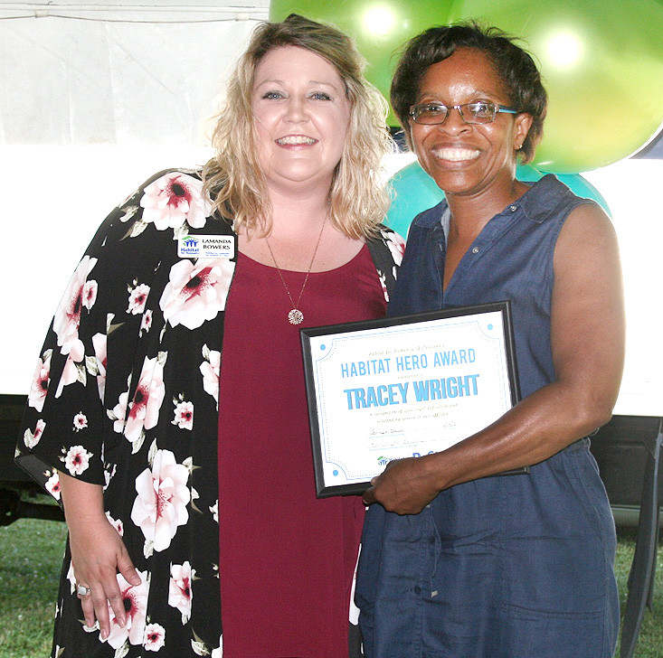 "TRACEY WRIGHT, right, was presented with the Habitat Hero Award by Habitat volunteer services manager LaManda Bowers, left. Bowers said Wright not only serves on the Women Build committee, but also raises funds to build homes, and volunteers at the job site regularly. ""Tracey is not an average person, she's extraordinary,"" Bowers said."