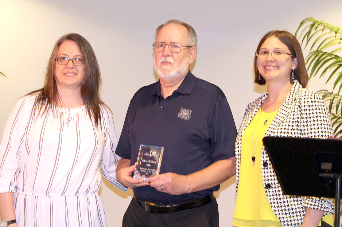 DAVID McELHANEY, center, was surprised with this year's Registration Department Award from The Caring Place. Joining him are receptionist Nolette Rose, left, and Corinne Freeman, interim executive director. Other award recipients (not available for photos) included Wayne Record, honored with the Food Department Award.