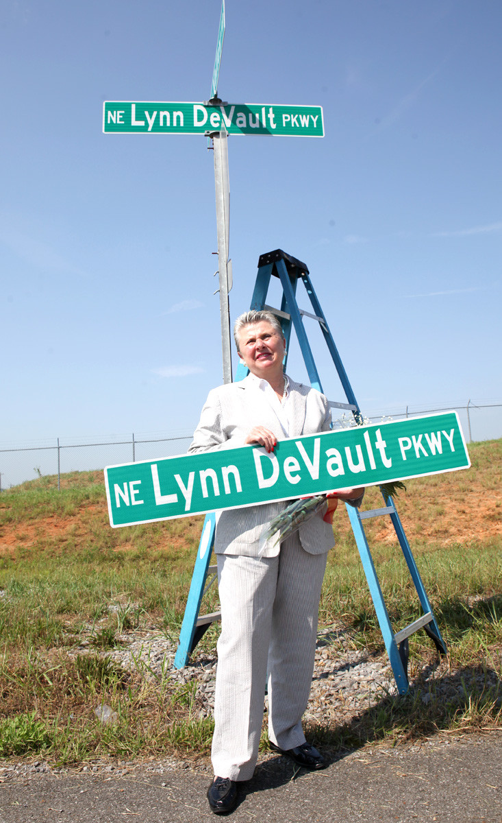 LYNN DEVAULT holds her keepsake road sign, in front of the official display of the new Lynn DeVault Partkway along the north end of the new Cleveland Jetport complex.