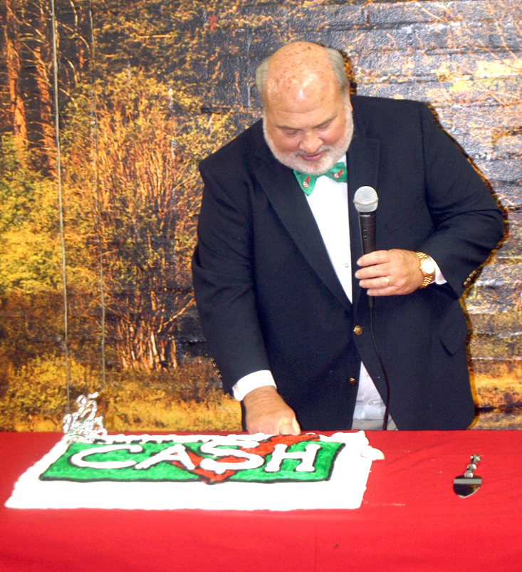 Jones is also shown cutting the colorful cake commemorating the 25th anniversary of Check Into Cash.