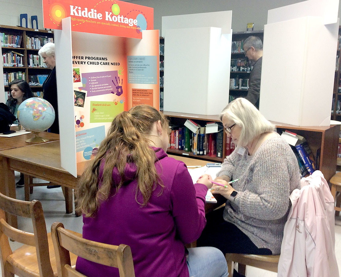 "At the Kiddie Kottage Day Care, Paula Armstrong helps ""parents"" with their child care plan."
