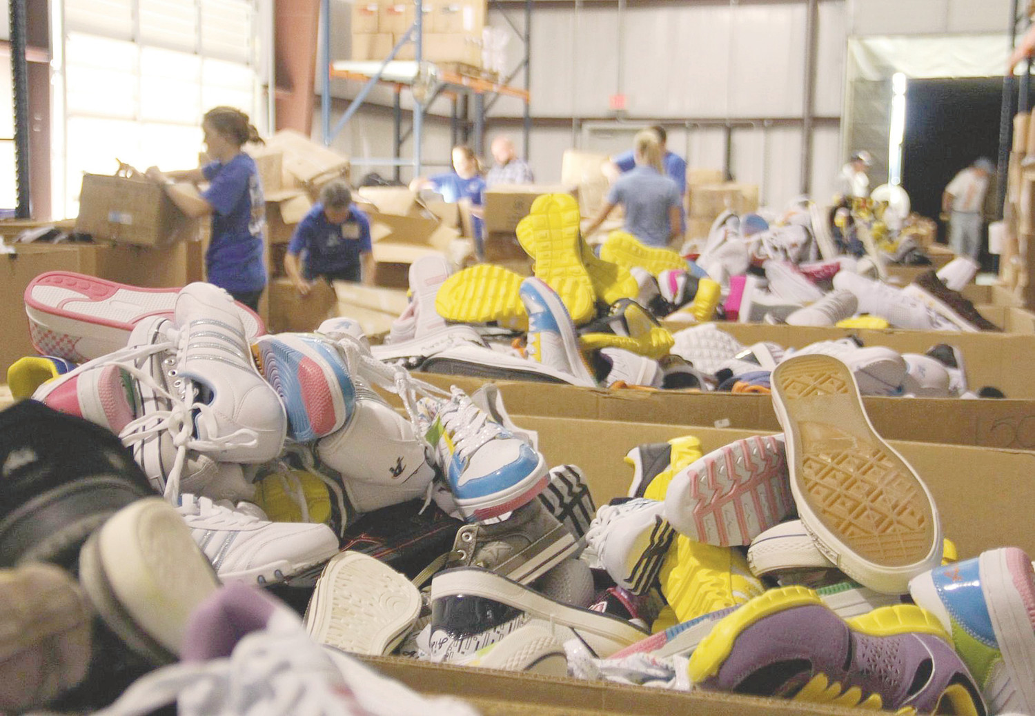 VOLUNTEERS sort through a huge collection of new shoes during a boxing party held in any number of U.S. cities in a previous campaign for Buckner Shoes For Orphan Souls. In the Cleveland and Bradley County community, the same type of boxing party takes place each year at Westwood Baptist Church. Locally, the Shoes for Orphan Souls campaign gets underway Wednesday and will continue throughout the month of August.