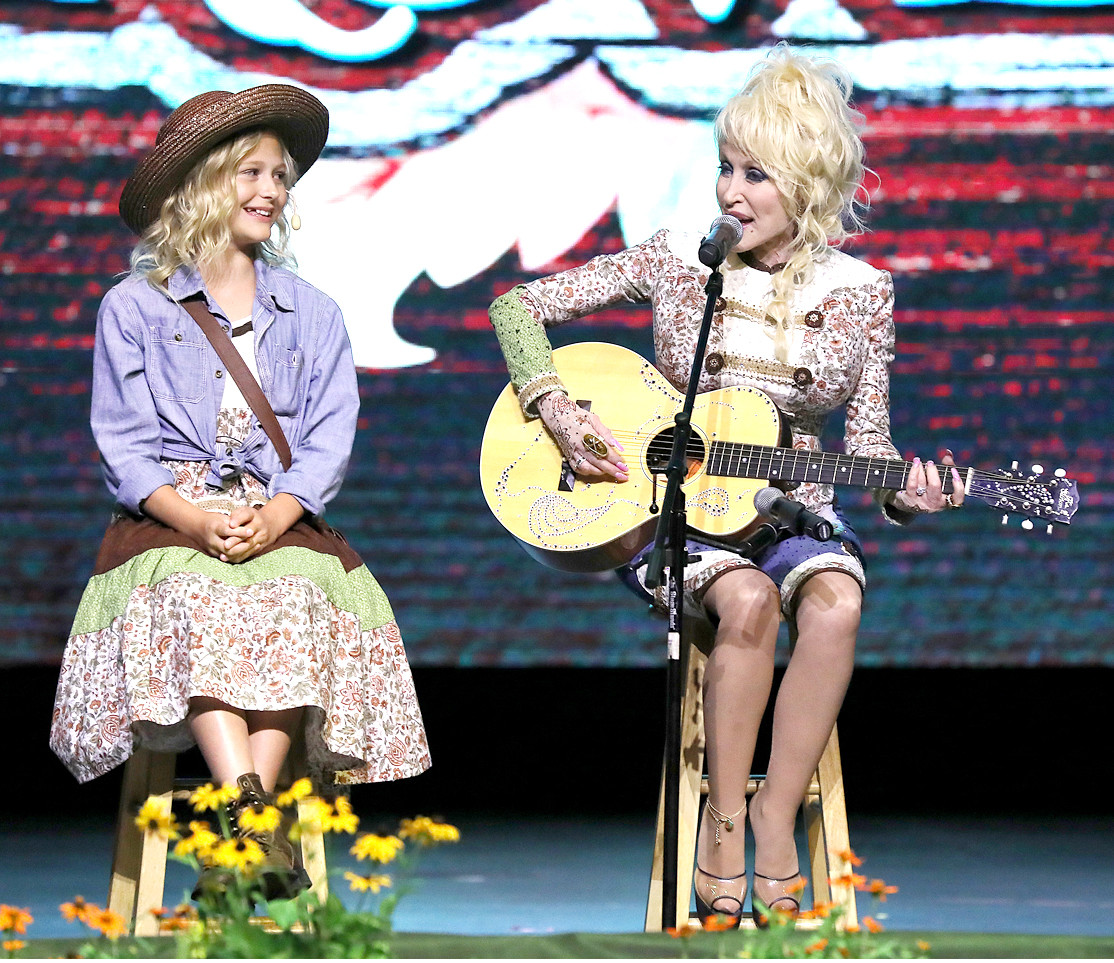 "DOLLY PARTON stands with young Alyvia Alyn Lind as the two perform the song ""Wildwood Grove"" in honor of the namesake new addition to Dollywood. Lind has performed in the ""Coat of Many Colors"" and ""Christmas of Many Colors"" films as a young version of Parton, and performed both songs ""Wildwood Grove"" and ""My Tennessee Mountain Home"" alongside Parton during Dollywood's Media Day on Friday."