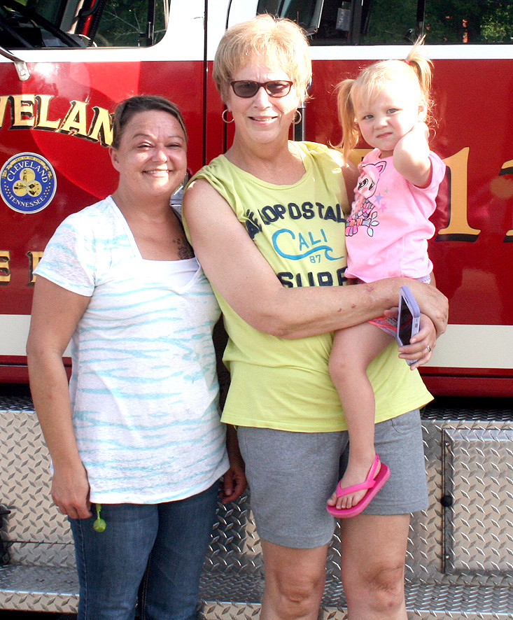ONE OF THE MOST interesting things that draws children to National Night Out is the inclusion of emergency response vehicles like this fire truck provided by the Cleveland Fire Department. From left are Nikki Ledwell, Kathy Foust and young Harper Price.