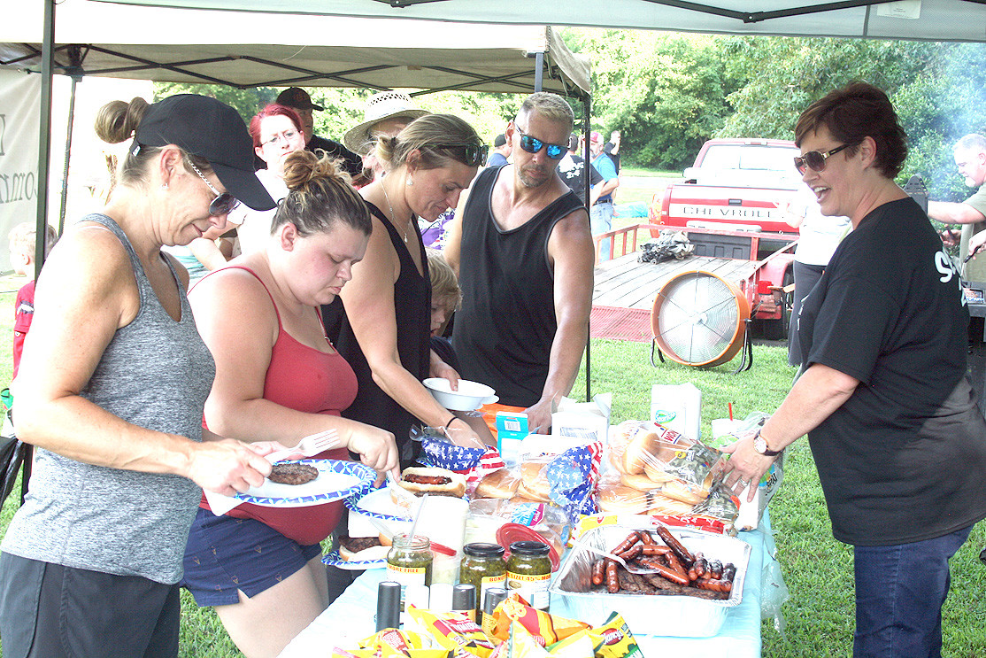 JENNIFER BUOL with Lake View Community Church serves hamburgers, hot dogs and condiments at Tuesday's National Night Out. Cooked by members of various churches, the food allows residents, church officials and even law enforcement to sit down together over a meal.