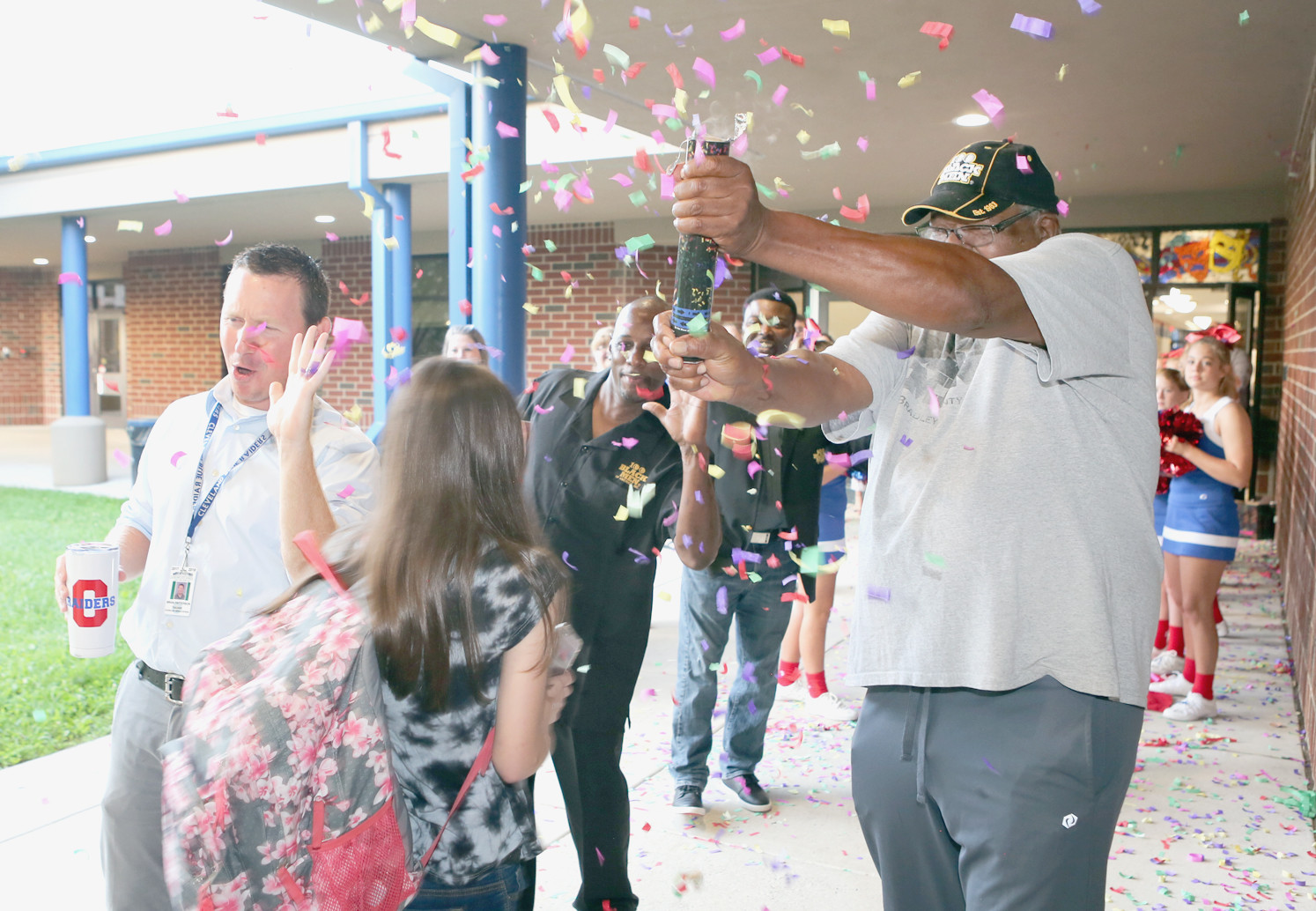 DON HUMES, a member of 100 Black Men of Bradley County Inc., right, pops a confetti cannon as some of the students are dropped off by car early Tuesday morning for the  first day of the 2018-19 school year at Cleveland Middle School.  Also cheering on the students, from left, are sixth-grade math teacher Brian Patterson, Jonathan Porter and Chuck Swafford.