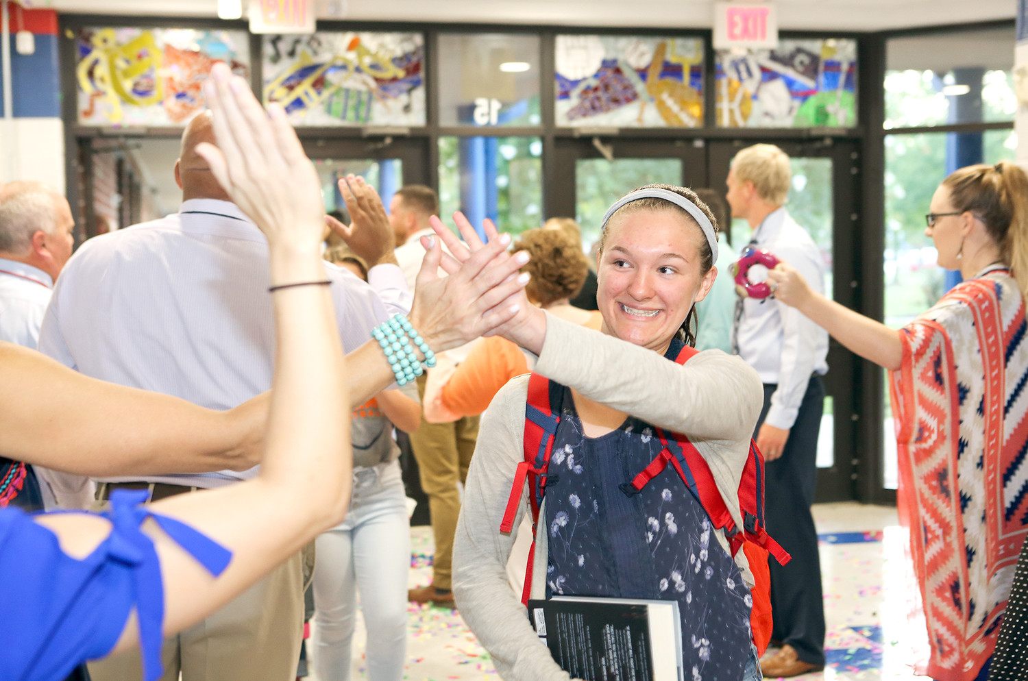 RETURNING CMS STUDENT Ella Lipscomb smiles brightly as she is greeted by a wall of teachers welcoming her back to Cleveland Middle School.