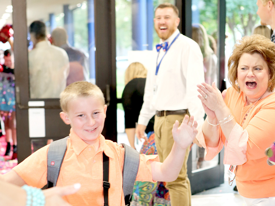 SPIRITED STUDENT Cory LeGrand left, slaps all the high-fives he's greeted with Tuesday morning at the Cleveland Middle School red carpet event.  Dr. Leneda Laing, right, cheers him on.