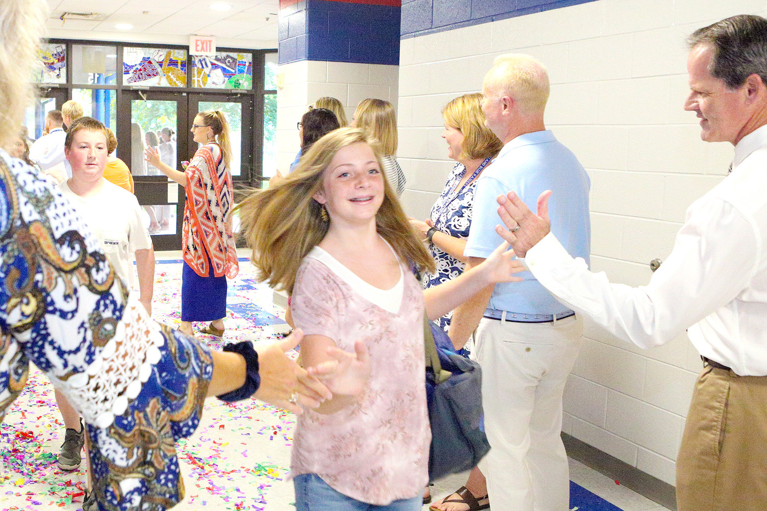CHEERFUL STUDENT Eliza Roe trots through the row of cheers and high-fives awaiting her as she enters Cleveland Middle School for the new school year.