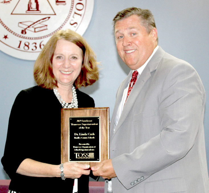 DR. LINDA CASH, director of Bradley County Schools, is presented with the Tennessee Organization of School Superintendents' Southeast Tennessee Superintendent of the Year award. Presenting the award is TOSS Executive Director Dr. Dale Lynch.