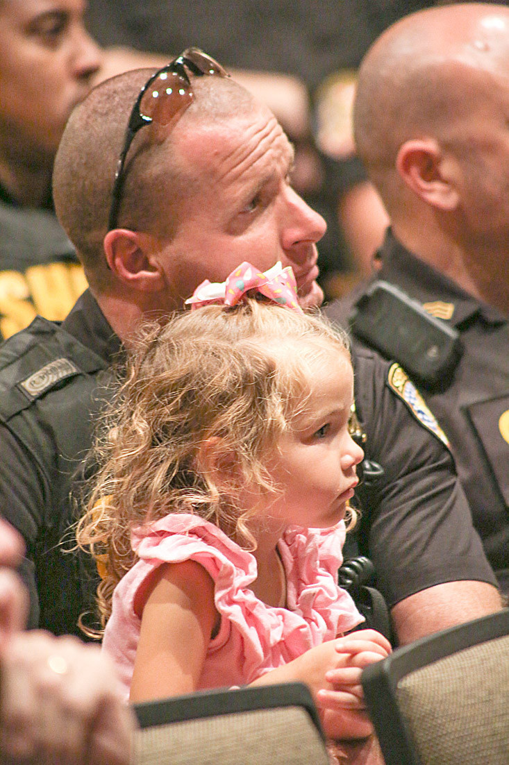 THIS LITTLE GIRL listens attentively with Sheriff's Deputy Eduardo Choate during the BCSO Swearing-In Ceremony on Saturday.