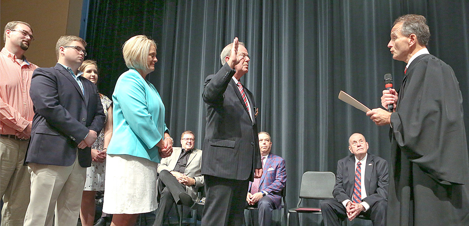JUDGE MIKE SHARP, right, administers the Oath of Sheriff to Steve Lawson, center, at Saturday's swearing-in ceremony while Lawson's family watches on. Watching from behind and pictured from left are speakers from the event Pastor Kelvin Page, Duane Gilbert and Mayor Tom Rowland.