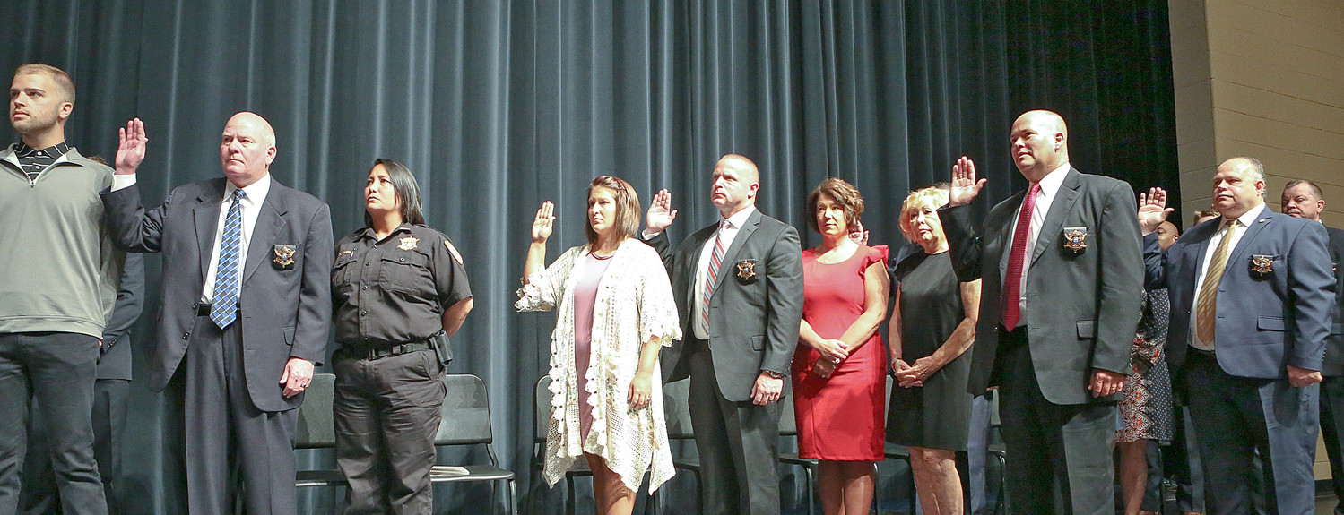 WITH SELECT FAMILY MEMBERS on stage as support, Sheriff Lawson's newly appointed Command Staff takes the Oath of Deputy Sheriff administered by Judge Andrew Freiberg.