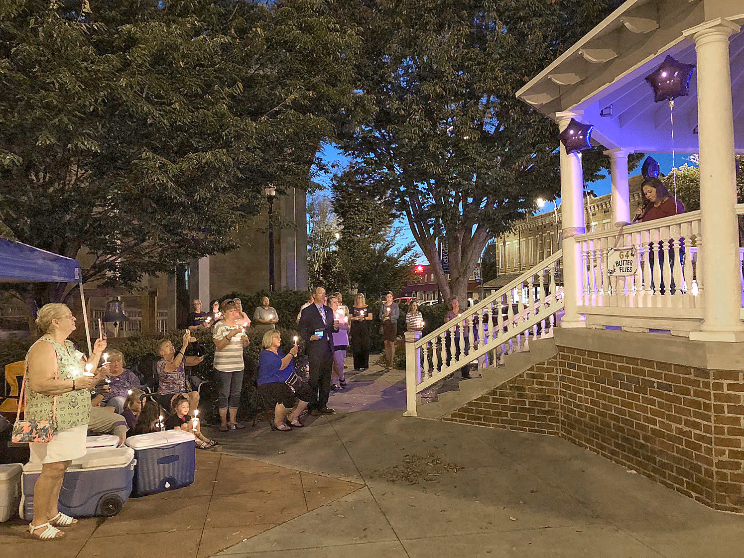 FAMILIES AND FRIENDS hold candles as they listen to Allison Branam read from a list of names of loved ones who have died from drug overdoses. The candlelight vigil was held Friday night in front of the Bradley County Courthouse.