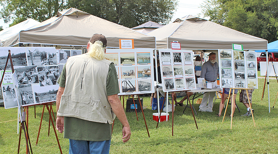 ONE OF THE VISITORS to Saturday's international Cowpea Festival and Cook-off in Charleston was busy viewing an assortment of photographs that were displayed showing historical buildings, people, events, bridges, and other structures in the Charleston and Calhoun communities.