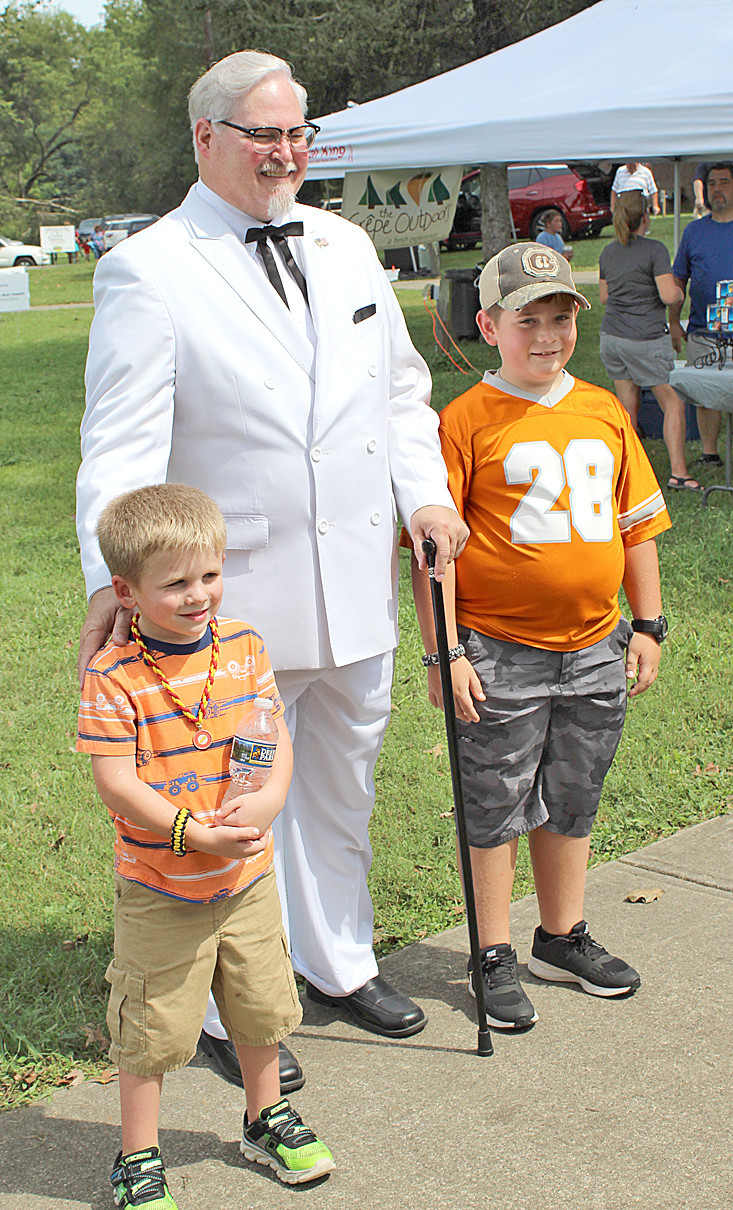 A COL. SANDERS look-alike spent his time at Charleston's International Cowpea Festival and Cook-off Saturday greeting festival-goers, and the many youngsters. Above, the colonel took time out for a photo with Charleston's Landon and Allen Qualls, the sons of Terry and Christal Qualls