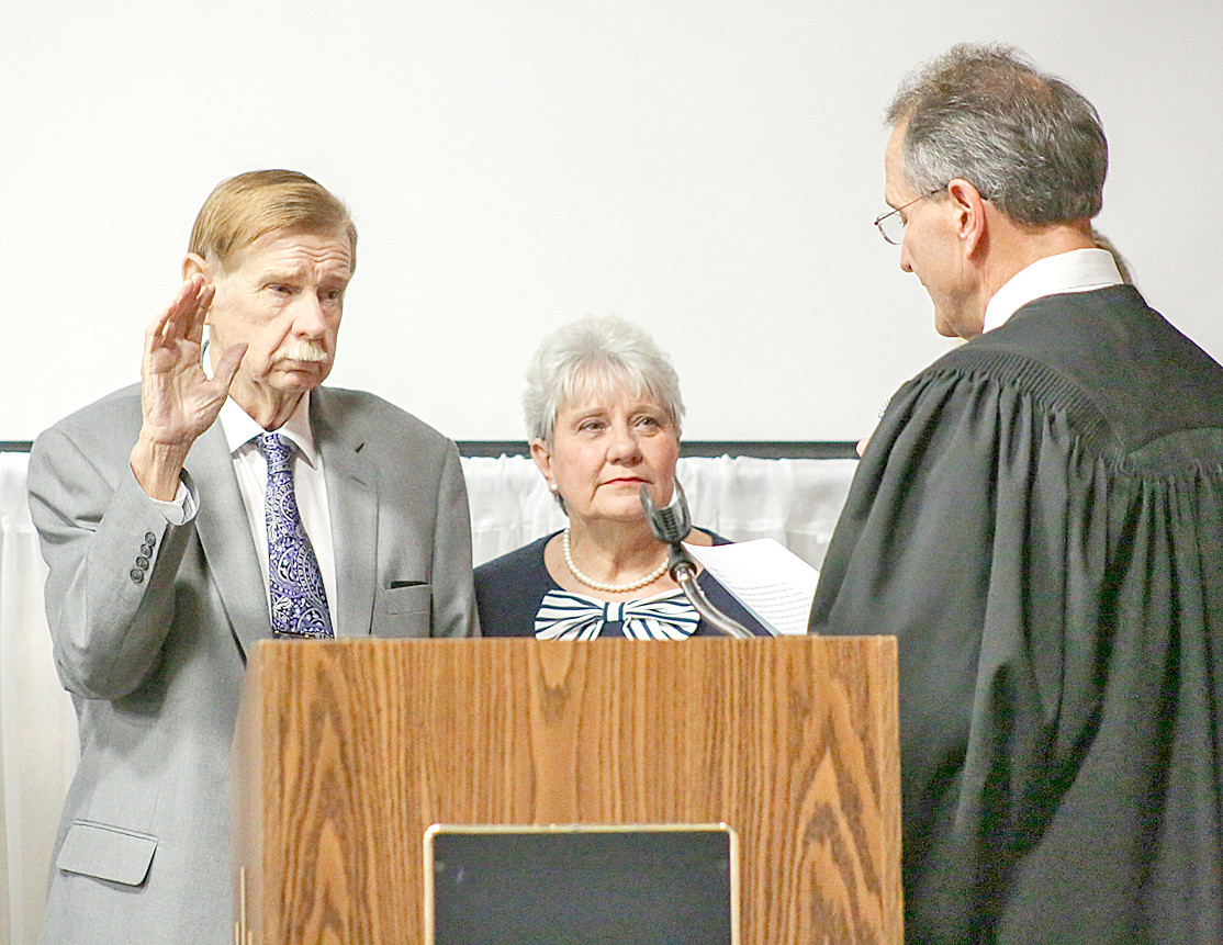 CLEVELAND CITY COUNCILMAN Charlie McKenzie, left, accompanied by family members and his wife, Marsha, takes the Oath of Office administered by Circuit Court Judge J. Michael Sharp at Monday afternoon's event at the Museum Center at Five Points.