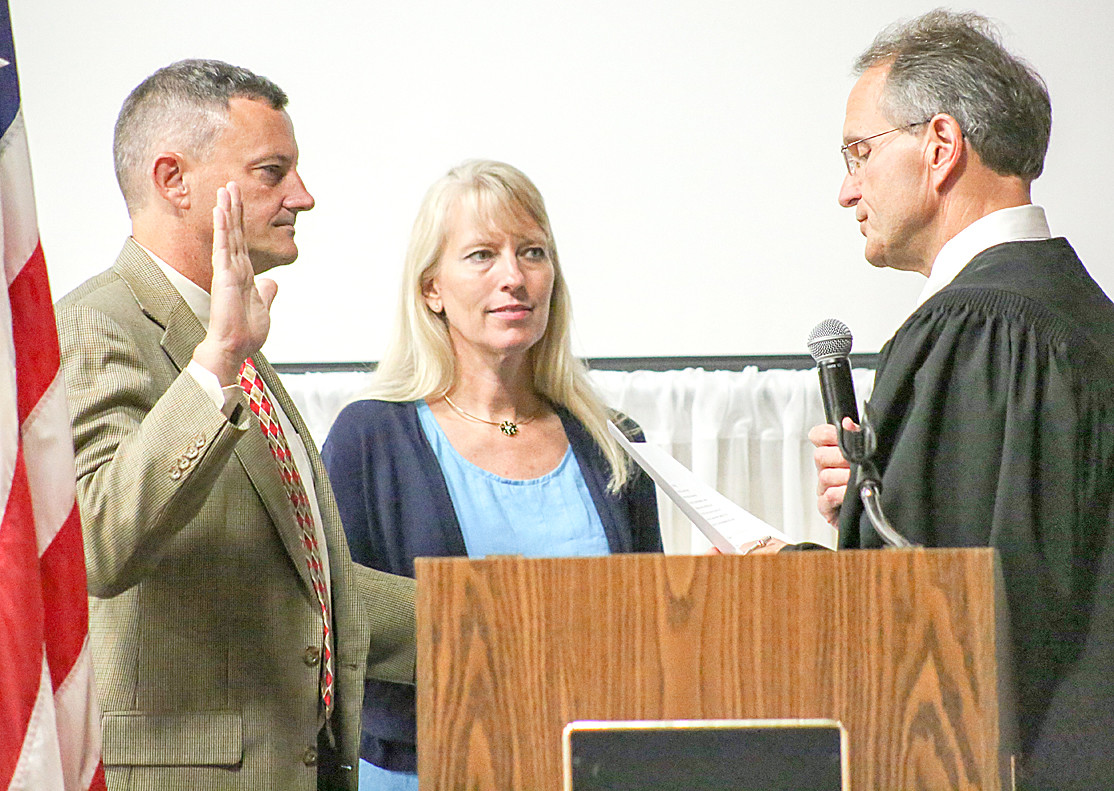 COUNCILMAN BILL ESTES, left, joined by his wife, Virginia, takes the Oath of Office administered by Circuit Court Judge J. Michael Sharp at Monday afternoon's event at the Museum Center at Five Points.
