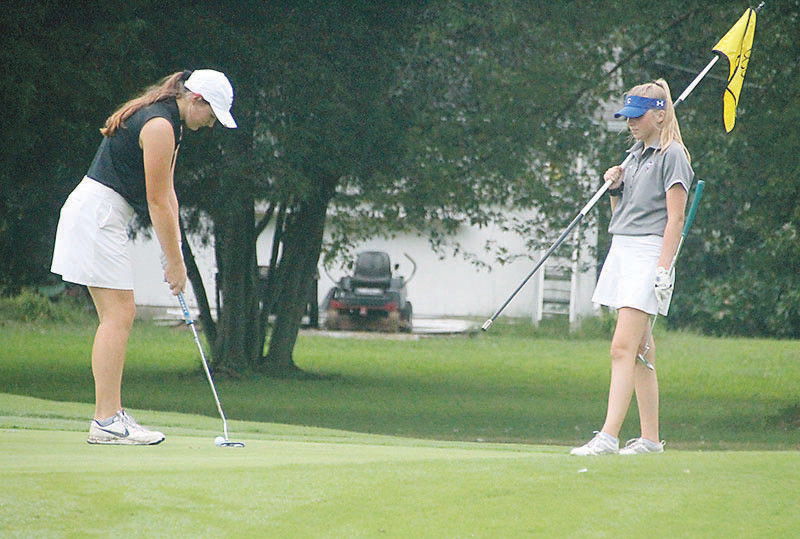 BRADLEY CENTRAL junior Cuppie Kyle taps in after chipping to within a few inches of the cup on the 14th green, while Cleveland High junior Ellie Mills holds the flag during Monday's District 5-Large Tournament at Cleveland Country Club.