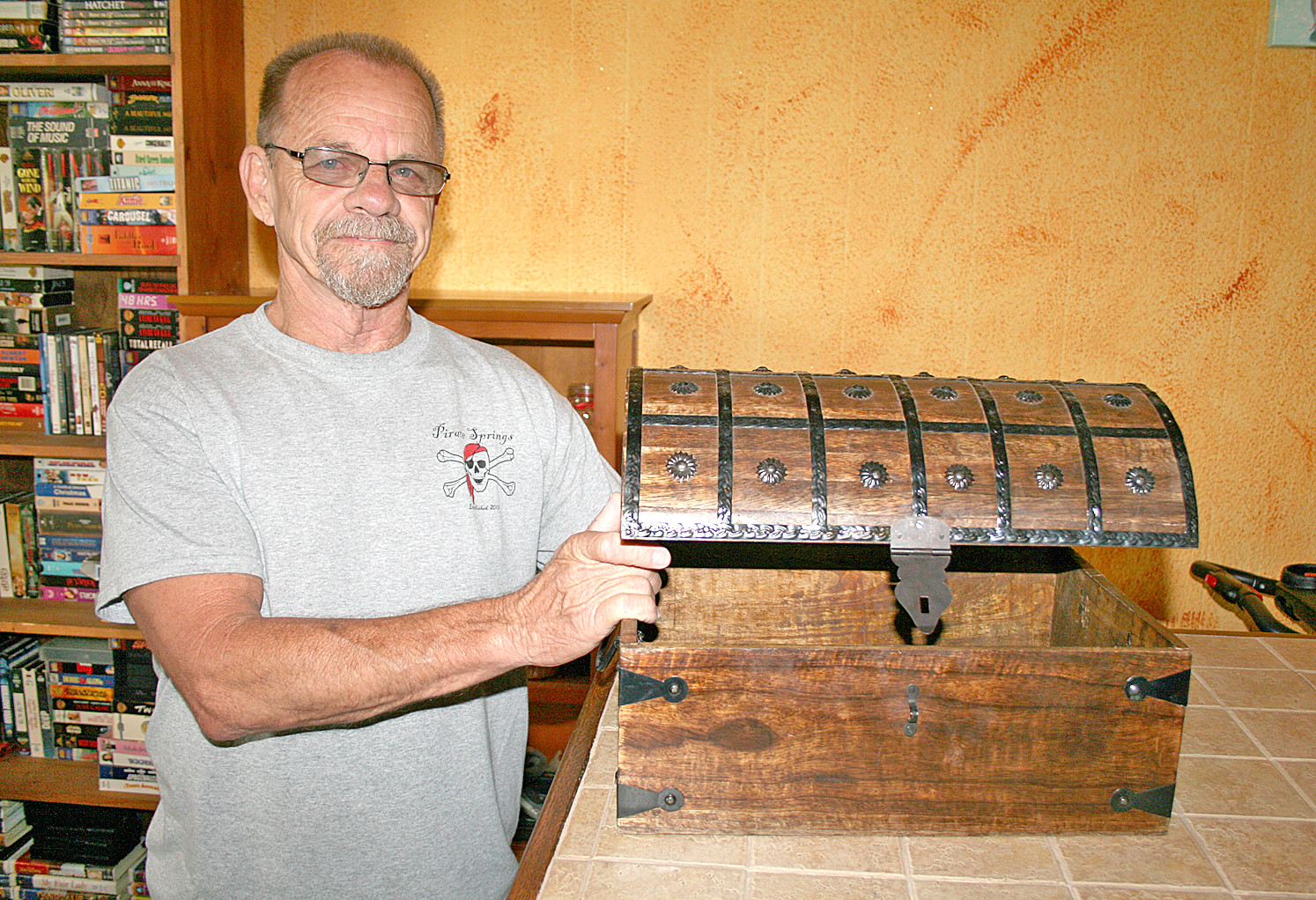 PAUL HOOK stands with a treasure chest, one of the numerous pirate-themed items that adorn the halls of Pirate Springs. Hook said he's trying to spread awareness of the program and its importance to the area, as him and his wife, Julie, have both been affected by addiction and feel led by God to aid those who suffer from it.