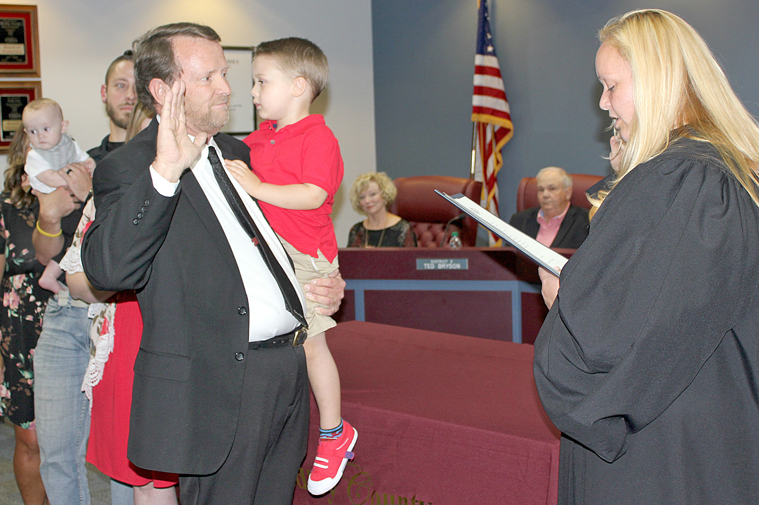 TROY WEATHERS, holding his grandson Jeremiah McDonald, is sworn in as the District 4 Bradley County Board of Education member by Magistrate Ashley Gaither.