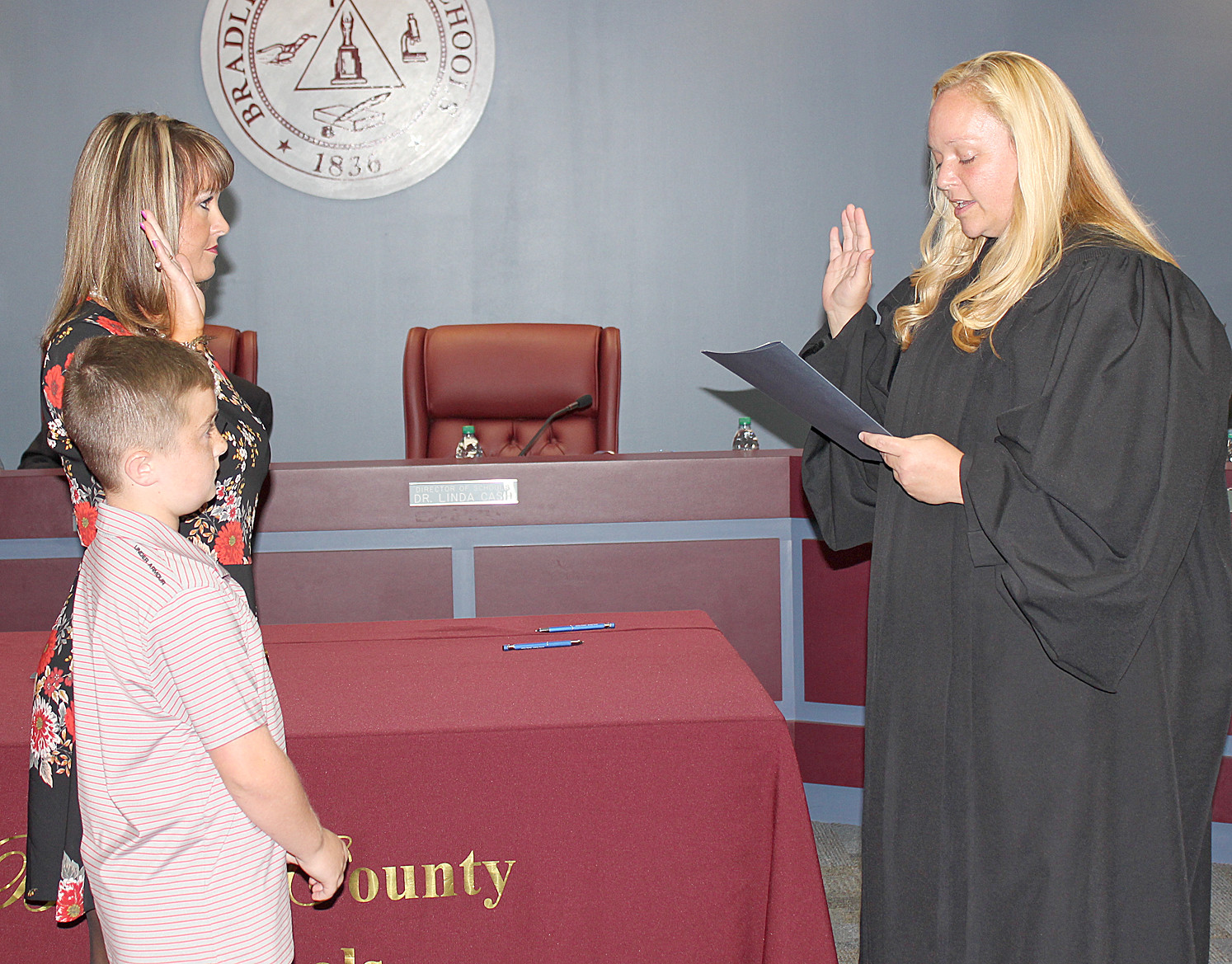 AMANDA LEE, accompanied by her son Axl, receives the Oath of Office from Magistrate Ashley Gaither after being re-elected as the District 6 Bradley County Board of Education member.