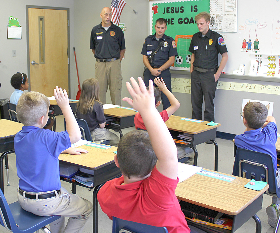 EAGER STUDENTS raise their hands to ask questions to guests visiting Shenandoah Baptist Academy for First Responders Appreciation Day.