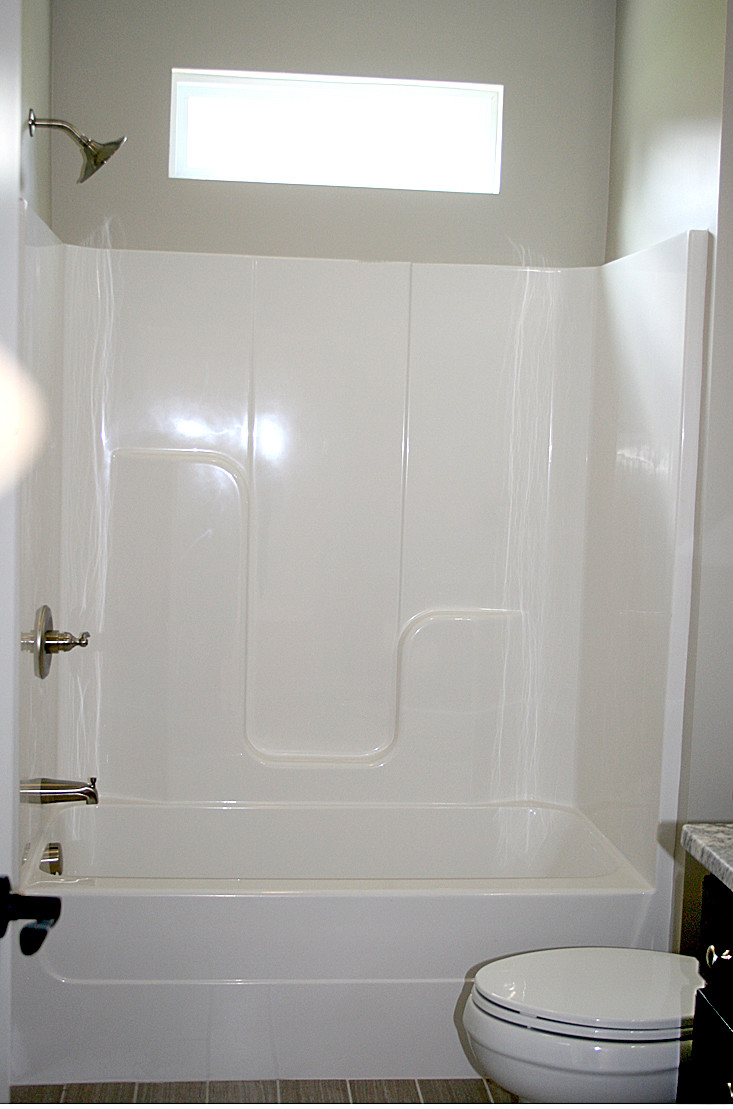 THE BATHROOM features a bath/shower tub fixture. A single window over the tub allows natural light.
