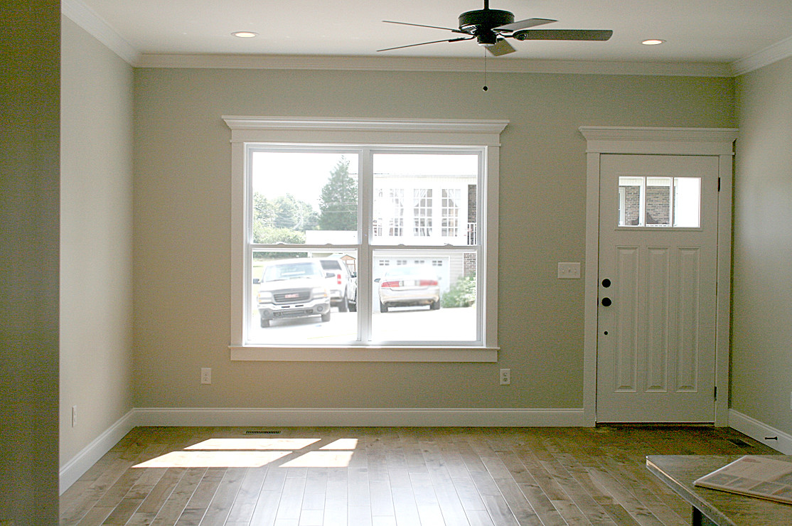 The living room features inset lights, a ceiling fan, beautiful hardwood flooring and crown molding along the ceiling and over the doors and windows.