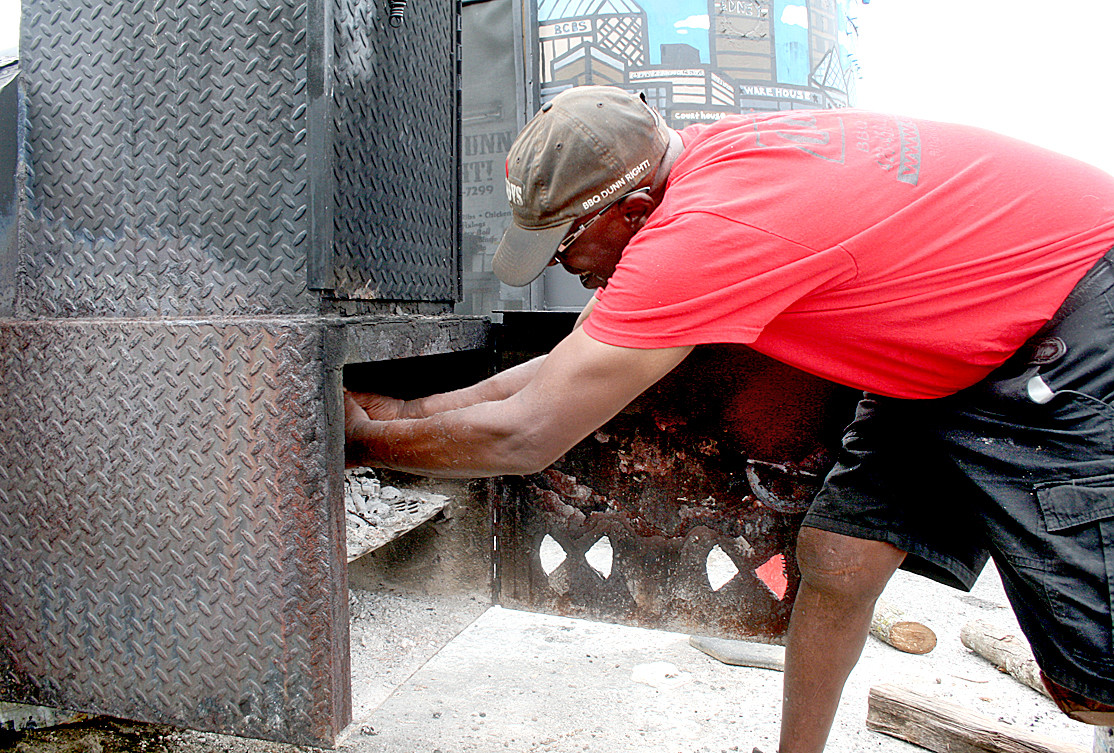 LOADING APPLEWOOD into his largest smoker, Anthony Dunn prepares the variety of flavors that will be infused into his smoked meat at GDaddy's BBQ Catering.
