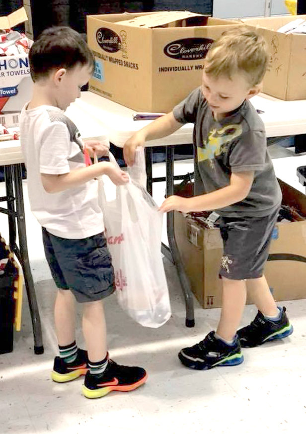 WORKING TOGETHER, two boys with Wesley Memorial United Methodist Church's preschool program help fill bags for the Sack Pack program. This program rallies volunteers of all ages to help feed children in need.