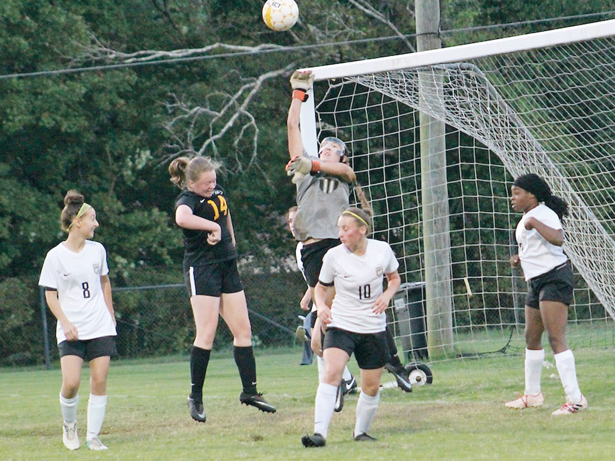 BRADLEY CENTRAL goalie Lillian Lawson jumps to deflect a shot by McMinn County in the District 5-AAA championship match in Athens on Thursday. Lawson saved a season high 17 shots.