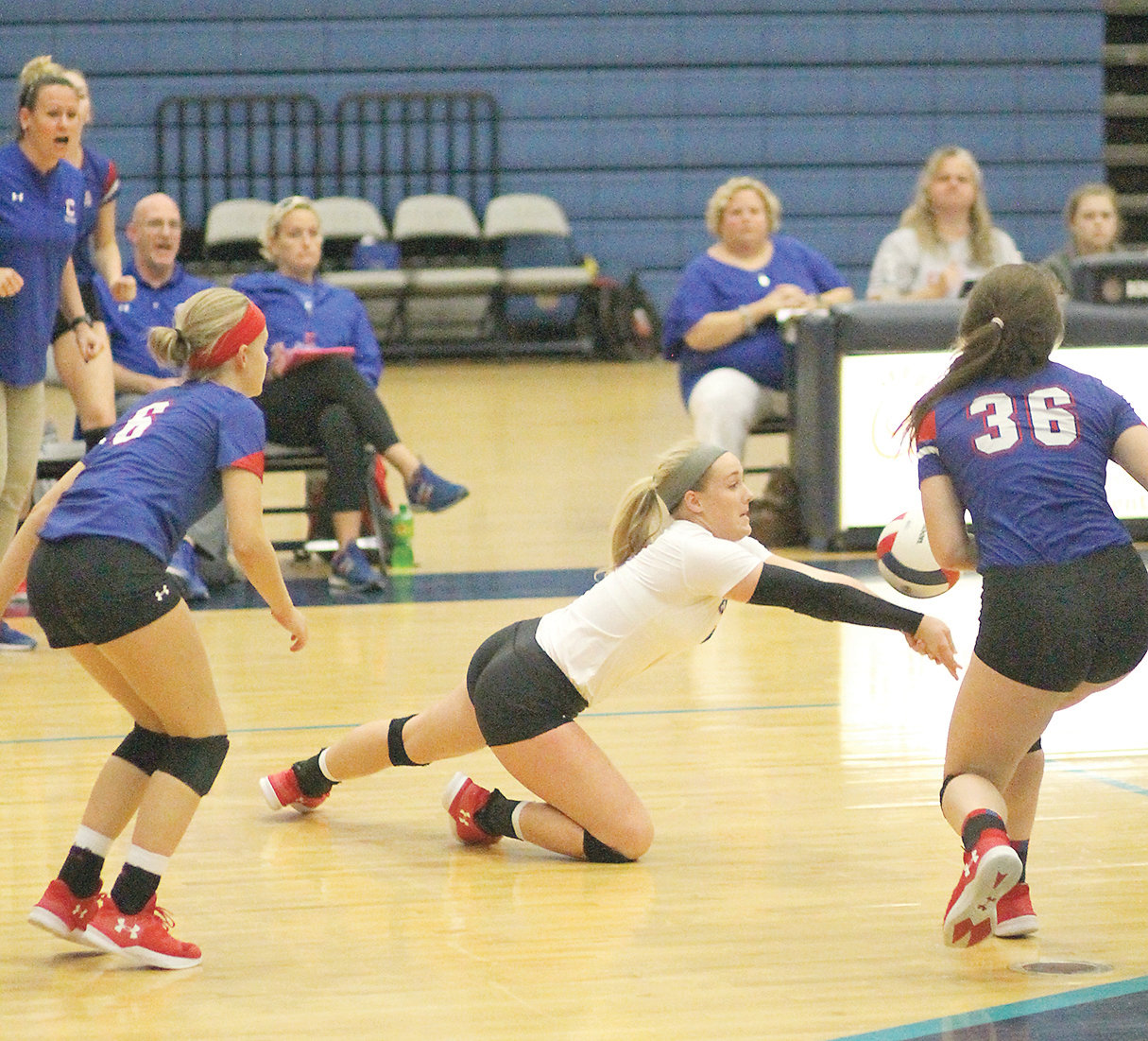 CLEVELAND SENIOR libero Lydia Martin (on floor) hits the deck to dig out a shot, while teammates Elliot Brock (6) and Anna Renshaw (36) close in during Thursday evening's TSSAA Sectional battle with Siegel in Murfreesboro.