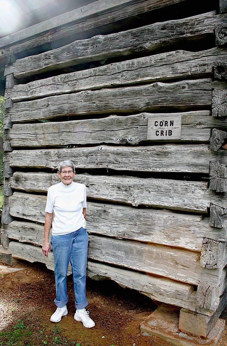 SALLY NEWMAN, owner and operator of the Village at Hawk Creek, stands in front of one of the village's original, 19th century buildings, the corn crib.